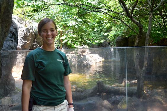 zoo keeper posing near otter exhibit