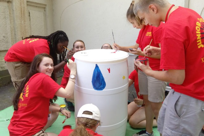 teen volunteers painting rain barrel