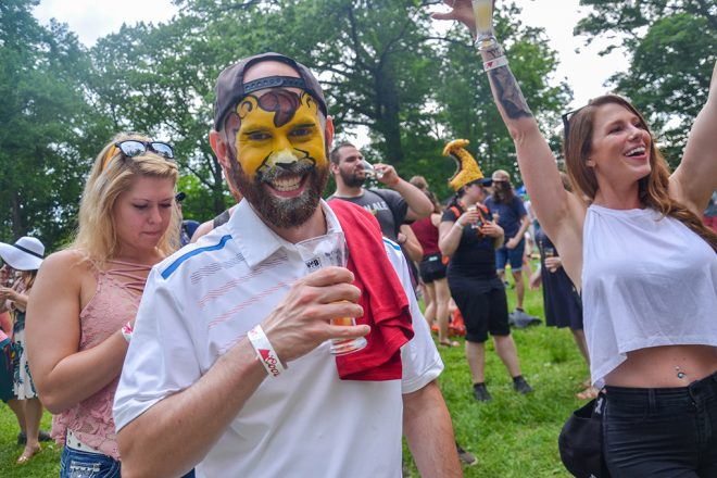 man with face paint holding beer glass