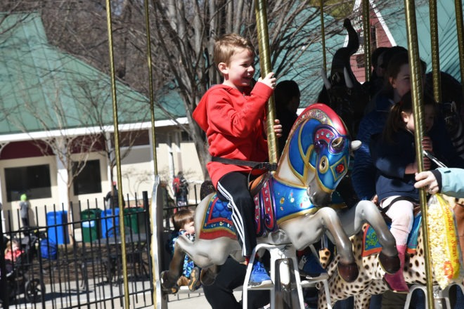 boy riding carousel
