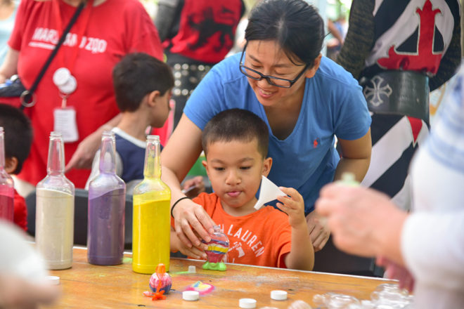 child doing sand art craft with parent