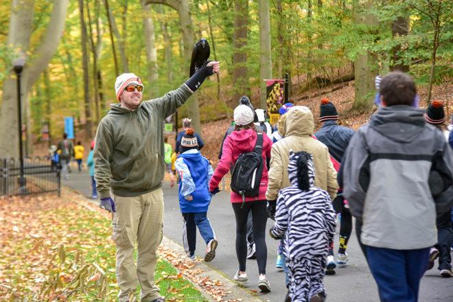 man holding raven as runners pass