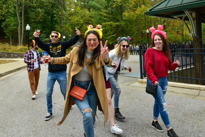group of people walking through zoo with beer mugs