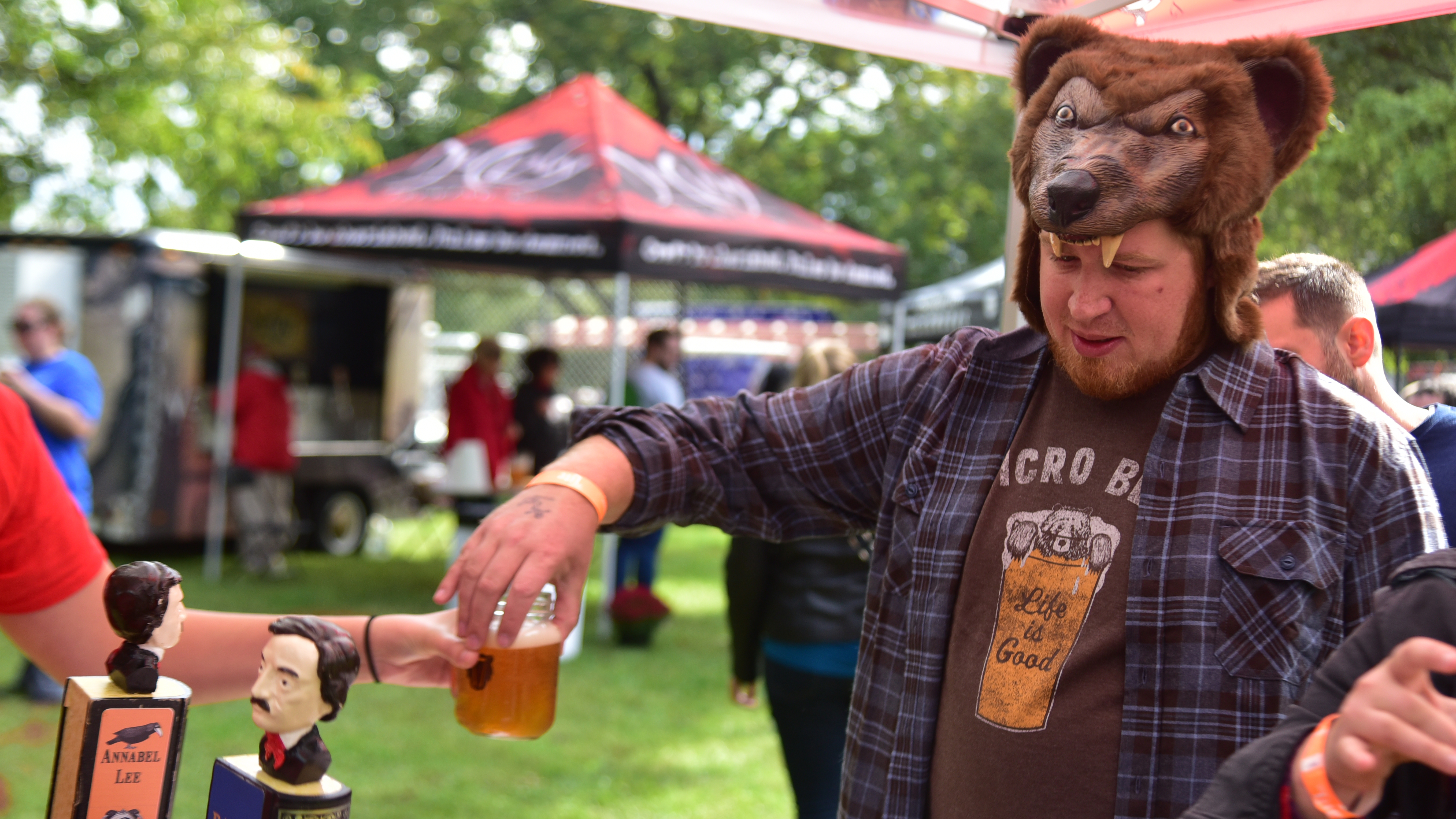 Man in bear hat being handed a beer